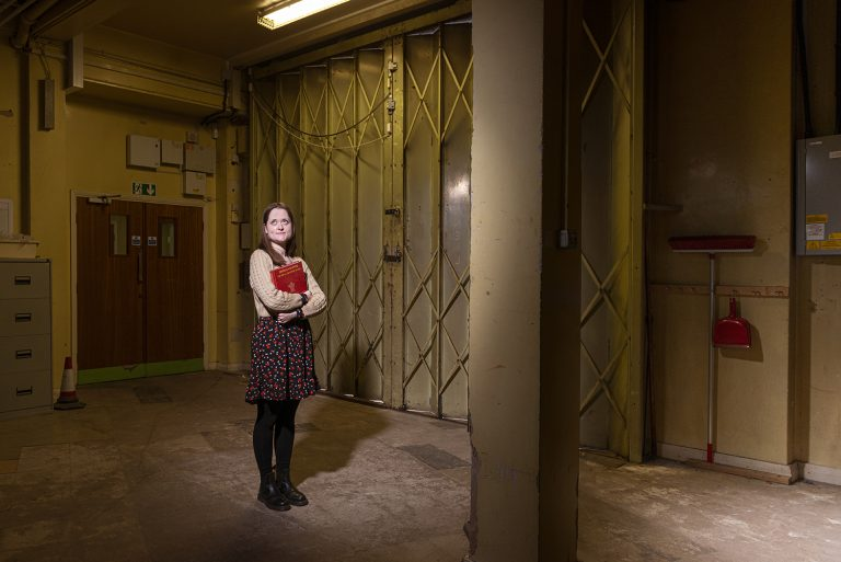 Robyn Coney, (Culture Development Assistant) holding a book about Thomas Crapper. This is the loading bay, accessed through the main foyer but not open to the public.  Every piece of artwork ever displayed here has passed through these doors.